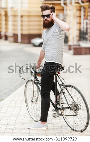 Confident and stylish. Full length of confident young bearded man adjusting eyewear and looking at camera while sitting on his bicycle outdoors - stock photo