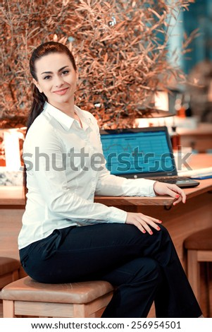Confident and successful business lady. Side view of beautiful young woman in formalwear smiling at camera while sitting at the bar  - stock photo