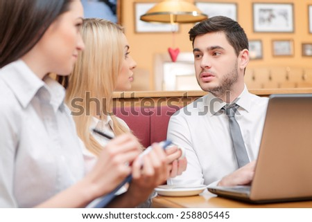 Confident and successful. Closeup of handsome young businessman in formalwear working on her laptop and talking with his female colleagues while sitting at the restaurant - stock photo