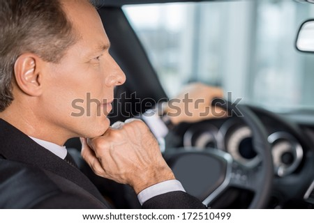Confident and successful. Confident mature man in formalwear sitting on drivers place in car and looking away - stock photo