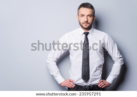 Confident and successful. Confident mature man in shirt and tie holding hands on hip and looking at camera while standing against grey background - stock photo