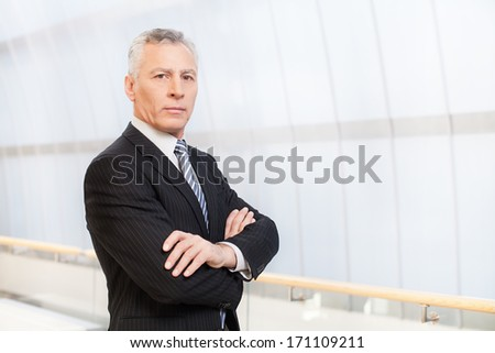 Confident and successful. Confident senior man in full suit holding hands in pockets and looking away - stock photo