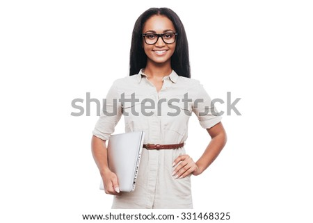Confident and successful. Confident young African woman in eyeglasses carrying laptop and smiling while standing against white background - stock photo