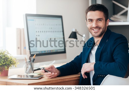 Confident and successful. Confident young man holding smart phone and smiling while sitting at his working place in office - stock photo