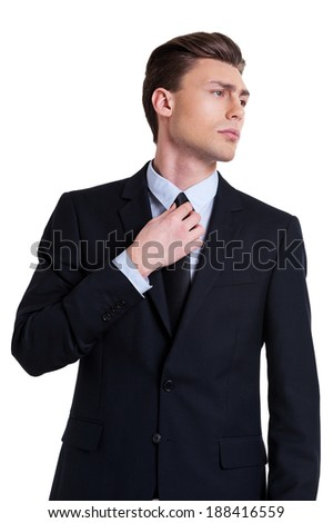 Confident and successful. Confident young man in formalwear adjusting his necktie and looking away while standing isolated on white - stock photo