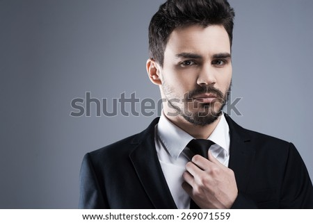 Confident and successful. Portrait of confident young man in formalwear looking at camera and adjusting his necktie while standing against grey background