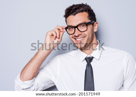 Confident and successful. Portrait of handsome young man in shirt and tie adjusting his eyeglasses and looking at camera while standing against grey background - stock photo