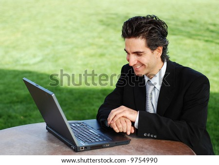 confident and successful young adult businessman working on his laptop computer