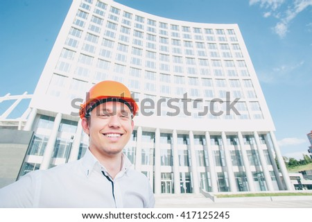 Confident architect. Handsome smiling young man in hardhat standing outdoors against building structure - stock photo