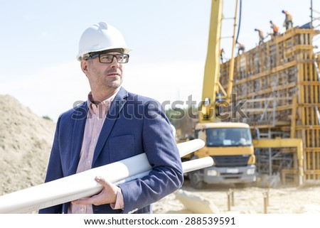 Confident architect holding rolled up blueprints at construction site - stock photo