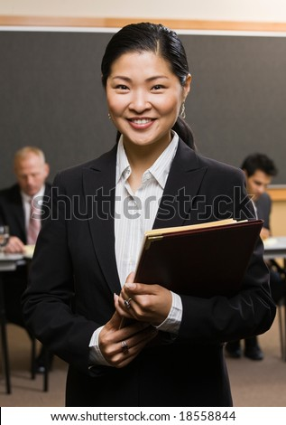 Confident Asian businessman holding files in front of co-workers in conference room - stock photo