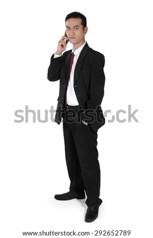Confident Asian businessman standing with one hand in pocket, looking to camera while making phone call, full body shot, isolated on white background - stock photo
