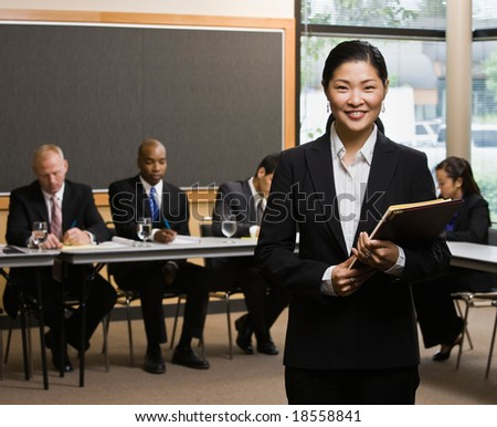 Confident Asian businesswoman standing in front of co-workers in conference room - stock photo