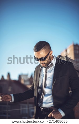 Confident attractive Arab businessman in urban environment with negative space - stock photo