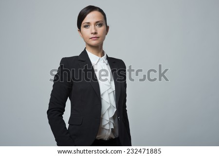Confident attractive businesswoman posing with hands in pockets. - stock photo