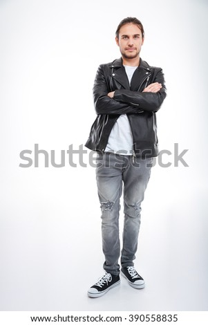 Confident attractive young man in leather jacket and jeans standing with arms crossed over white background - stock photo