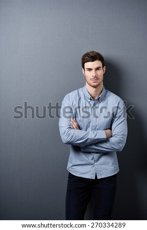 Confident Attractive Young Man with Arms Crossing Over his Chest Standing In Front a Gray Wall While Staring at the Camera. - stock photo