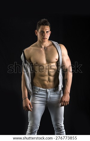 Confident, attractive young man with open vest on muscular torso, ripped abs and pecs. Isolated on black - stock photo