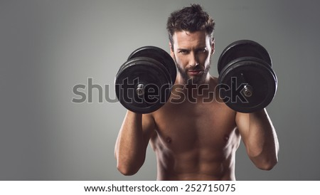 Confident attractive young man working out and weightlifting with dumbbells - stock photo