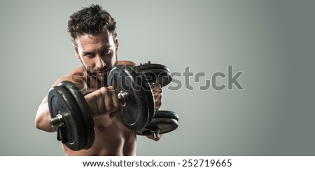 Confident attractive young man working out and weightlifting with dumbbells