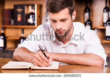 Confident bar owner. Confident young male bartender in white shirt leaning at the bar counter and writing something in note pad - stock photo