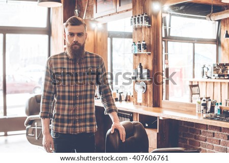 Confident barber expert. Young bearded man looking at camera and keeping hand on chair while standing at barbershop - stock photo
