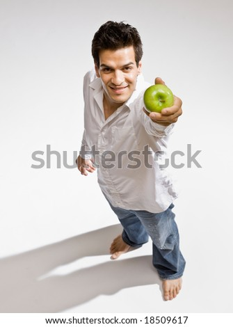 Confident barefoot man holding fresh wholesome green apple - stock photo