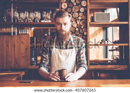 Confident barista. Young bearded man in apron looking at camera and holding coffee cup while standing at bar counter - stock photo