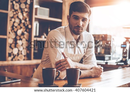 Confident barista. Young handsome man in apron looking at camera while leaning to bar counter at cafe - stock photo
