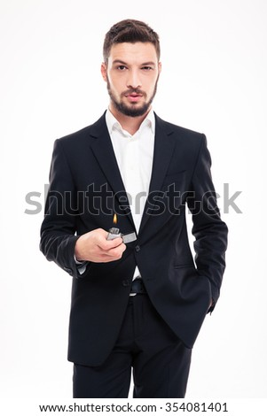 Confident bearded young business man in black suit and white shirt standing and holding gas lighter over white background - stock photo