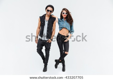 Confident beautiful young couple standing together over white background - stock photo