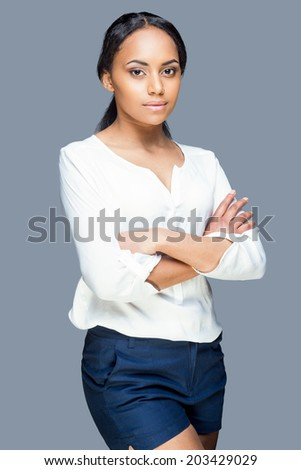 Confident beauty. Attractive young African woman keeping arms crossed and looking at camera while standing against grey background - stock photo
