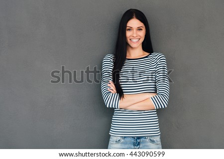Confident beauty. Attractive young woman keeping arms crossed and looking at camera with smile while standing against grey background - stock photo