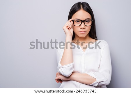 Confident beauty. Beautiful young Asian woman in eyewear looking at camera and keeping arms crossed while standing against grey background - stock photo