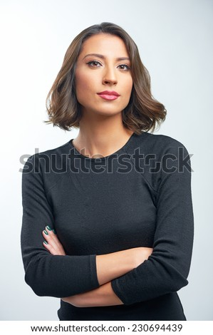 Confident beauty. Beautiful young caucasian woman looking at camera and keeping arms crossed while standing over white background - stock photo