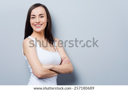 Confident beauty. Beautiful young woman looking at camera and keeping arms crossed while standing against grey background - stock photo