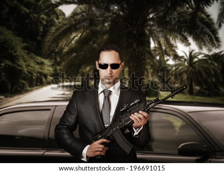 Confident bodyguard wearing sunglasses while standing against limousine and holding automatic.  - stock photo