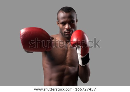 Confident boxer. Confident young African boxer in boxing gloves stretching out his hand and looking at camera while standing isolated on grey - stock photo