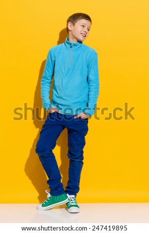 Confident boy. Young boy posing with hands in pockets. Full length length studio shot on yellow background. - stock photo