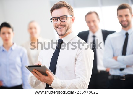 Confident business expert. Confident young businessman holding digital tablet and smiling while his colleagues standing in the background  - stock photo