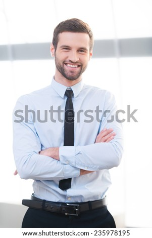Confident business expert. Confident young businessman keeping arms crossed and smiling while standing indoors - stock photo
