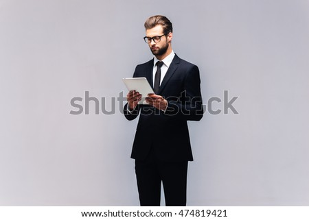 Confident business expert. Studio shot of handsome young man in full suit working on digital tablet