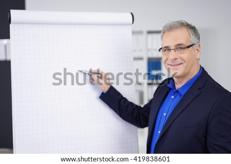 Confident business giving a presentation at the office standing in front of blank flip chart pointing with a pen while smiling at the camera - stock photo