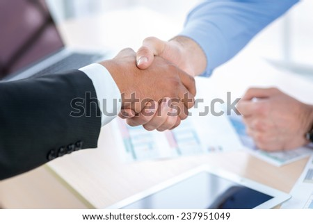 Confident business handshake. Close-up view of a handshake while two successful businessman shaking hands at the table against each in the business office in formal wear and work at a laptop.