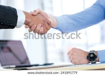 Confident business handshake. Two Confident businessman sitting at the negotiating table in the office and shaking hands close-up view of hands. Business people dressed in formal wear - stock photo