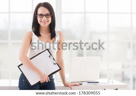 Confident business lady. Beautiful young woman in glasses holding clipboard and smiling while leaning at the table - stock photo