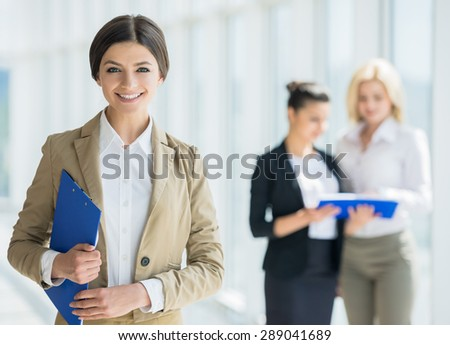 Confident business lady in suit standing in front of her partners and smiling. - stock photo