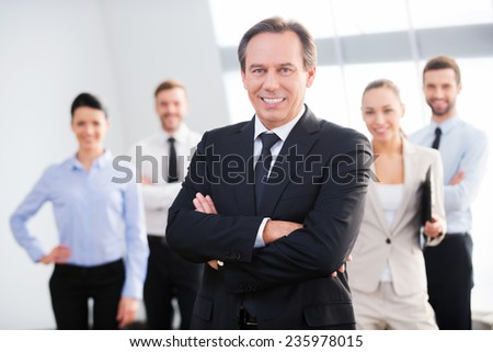 Confident business leader. Confident mature businessman keeping arms crossed and smiling while his colleagues standing in the background  - stock photo