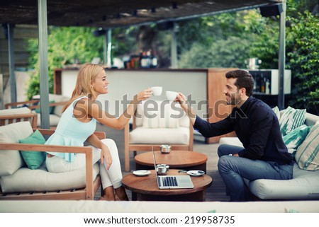 Confident business man and business woman at meeting outdoors, business partners smiling while drinking coffee and talking about good idea, young people clinking cups while smiling at business lunch - stock photo