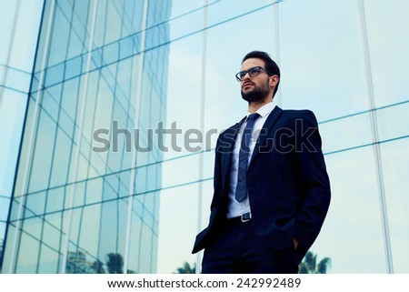 Confident business man in glasses standing against office building with hands in the pockets - stock photo